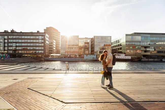 Pareja abrazándose mientras está de pie en el paseo marítimo en la ciudad durante el verano - foto de stock