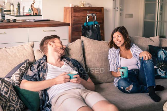Coppia che parla mentre si gode il caffè sul divano in appartamento — Foto stock