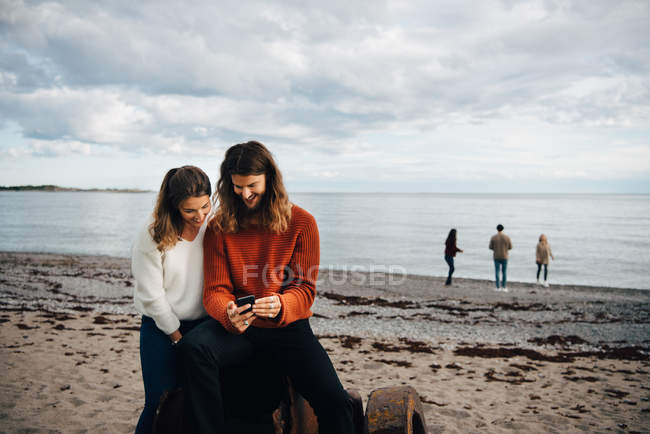 Couple looking at mobile phone while sitting on sea shore at beach — Stock Photo