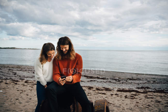 Smiling man showing mobile phone to woman while sitting at beach — Stock Photo