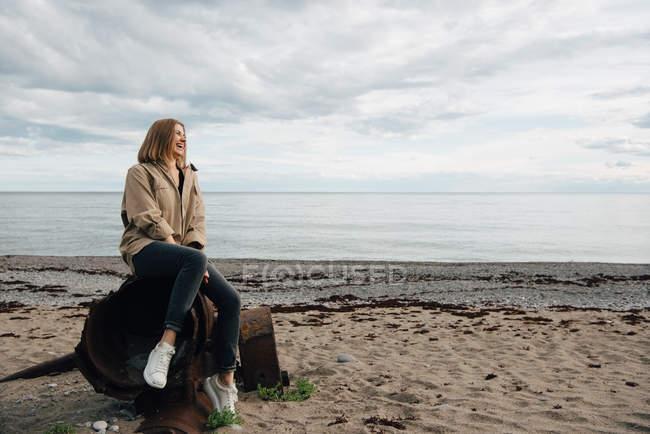 Mujer joven y alegre sentada sobre metal teñido en la playa contra el cielo - foto de stock