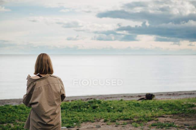 Vista posteriore della donna che guarda il mare contro il cielo — Foto stock