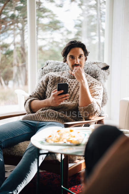 Portrait of smiling man with smart phone sitting on armchair at home — Stock Photo