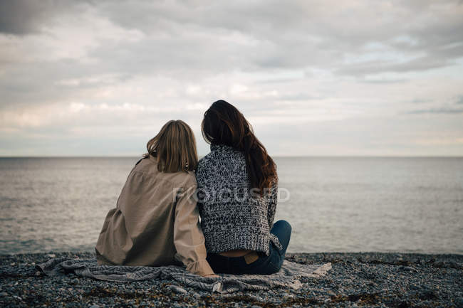 Rear view of female friends spending leisure time at beach against cloudy sky — Stock Photo