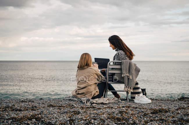 Amigos do sexo feminino usando tecnologias enquanto se sentam na praia contra o céu nublado — Fotografia de Stock