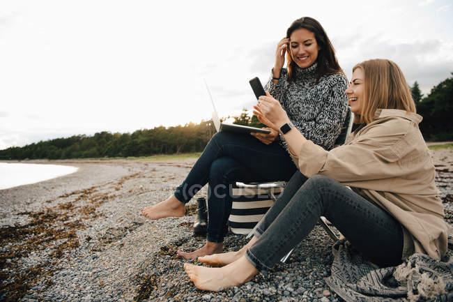 Amigos felices mirando el teléfono inteligente mientras están sentados en la playa contra el cielo - foto de stock