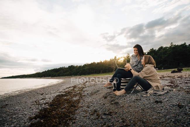 Amigos femeninos mirando el teléfono móvil mientras están sentados juntos en la playa durante el atardecer - foto de stock