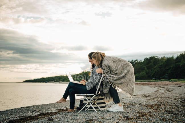 Amigo saudação mulher trabalhando no laptop enquanto sentado na praia contra o céu — Fotografia de Stock