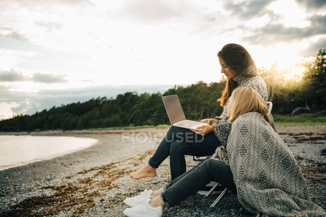 Mujer envuelta en una manta mirando a un amigo usando un ordenador portátil en la orilla del mar - foto de stock