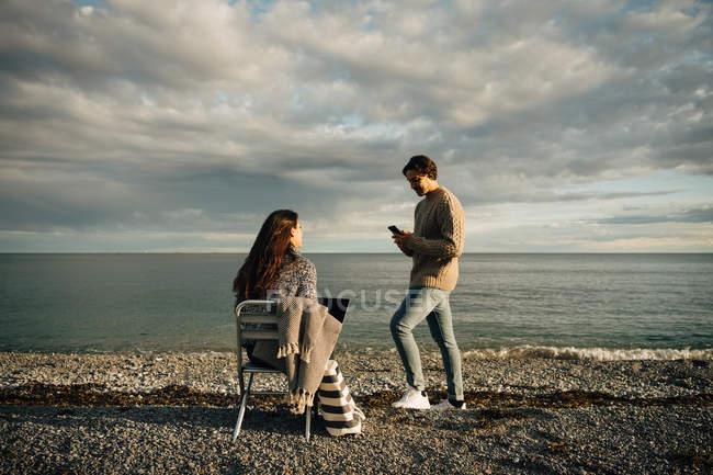 Homem usando telefone celular enquanto mulher sentada com laptop na cadeira na praia contra o céu — Fotografia de Stock