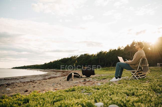 Взрослый мужчина, использующий ноутбук, сидя на берегу на пляже против неба — стоковое фото