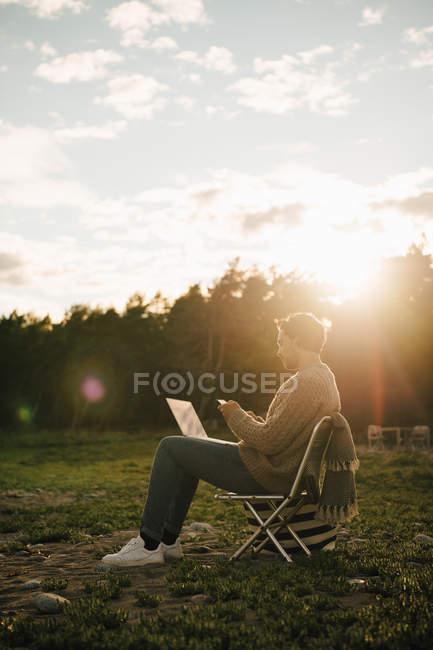 Comprimento total do homem com laptop usando telefone celular enquanto sentado na cadeira durante o pôr do sol — Fotografia de Stock