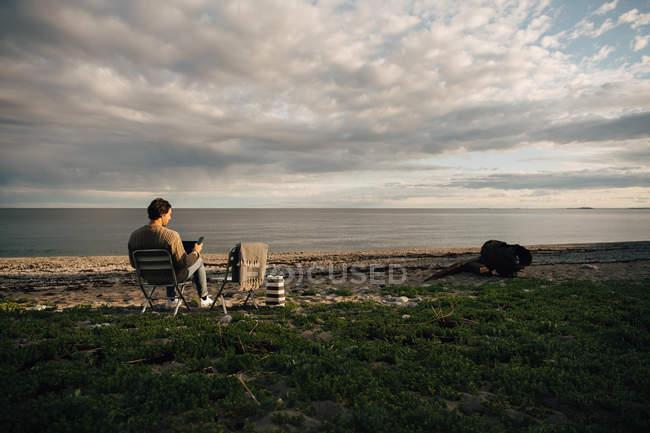 Comprimento total do homem usando laptop e telefone celular enquanto sentado na praia contra o céu nublado — Fotografia de Stock