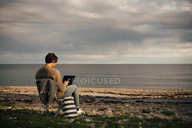 Homem adulto médio usando laptop e telefone celular enquanto sentado na costa do mar na praia contra o céu — Fotografia de Stock