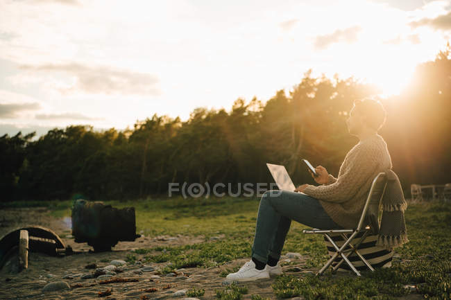 Full length of thoughtful man with laptop and mobile phone sitting on chair during sunset — Stock Photo