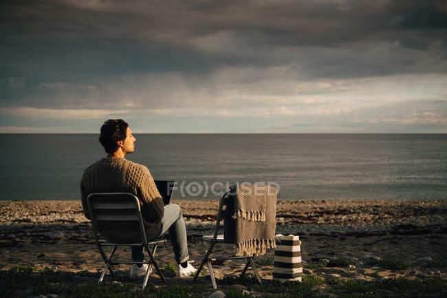 Homem pensativo usando laptop enquanto sentado na praia contra o céu nublado — Fotografia de Stock