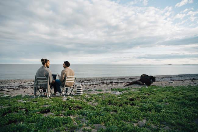 Amigos homens discutindo sobre laptop enquanto sentados em cadeiras na praia contra o céu — Fotografia de Stock