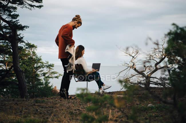 Homem segurando cobertor enquanto mulher usando laptop na floresta contra o céu — Fotografia de Stock
