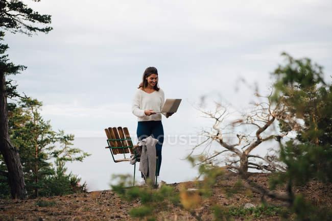 Sorrindo jovem mulher com laptop em pé por cadeira na floresta contra o céu — Fotografia de Stock