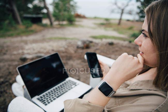 Thoughtful woman with smart phone and laptop sitting outdoors — Stock Photo