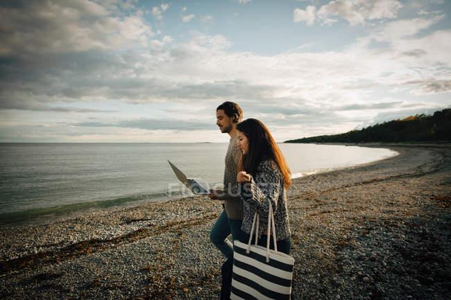 Mulher andando com homem usando laptop na costa do mar na praia contra o céu — Fotografia de Stock