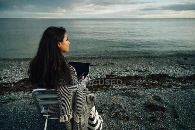 Mulher atenciosa com laptop sentado na cadeira na praia durante o pôr do sol — Fotografia de Stock