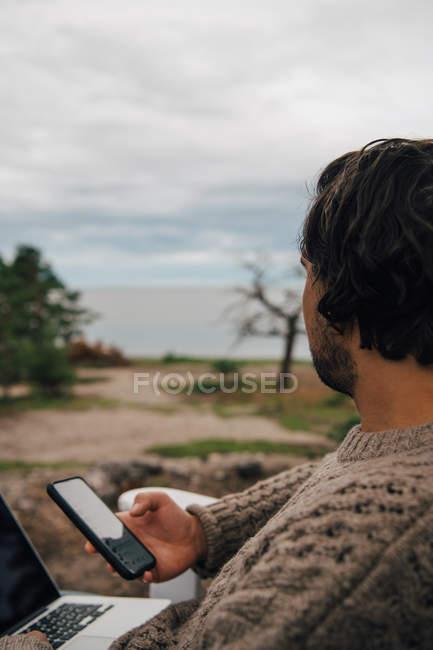 Close-up de homem com mensagens de texto laptop no telefone enquanto olha para o exterior — Fotografia de Stock