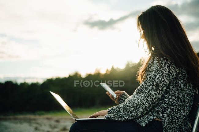 Mujer adulta con mensajería de texto portátil sentada en la playa al atardecer - foto de stock