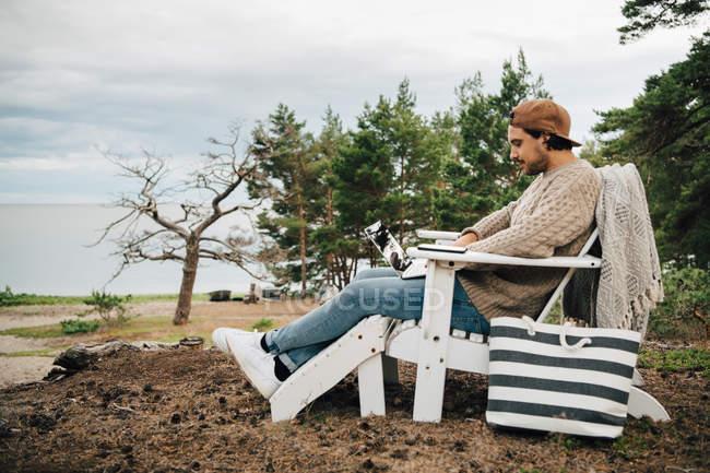 Vista lateral del hombre usando el ordenador portátil mientras está sentado en la silla Adirondack en el bosque - foto de stock
