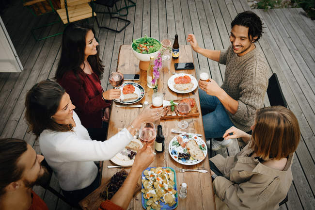 High angle view of friends enjoying drinks while having food during garden party — Stock Photo