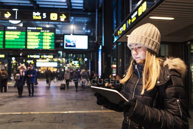 Девушка-подросток, стоящая в городе зимой с помощью цифрового планшета — стоковое фото
