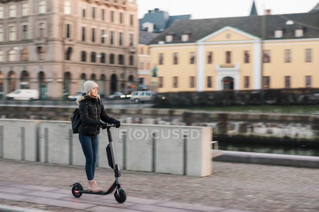 Longitud completa de la adolescente montando e-scooter en la calle en la ciudad - foto de stock