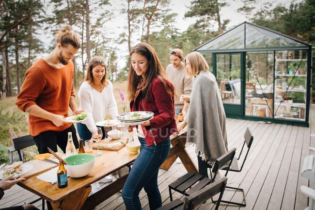 Amici maschi e femmine che trasportano gli avanzi di piatti dopo cena nel patio — Foto stock
