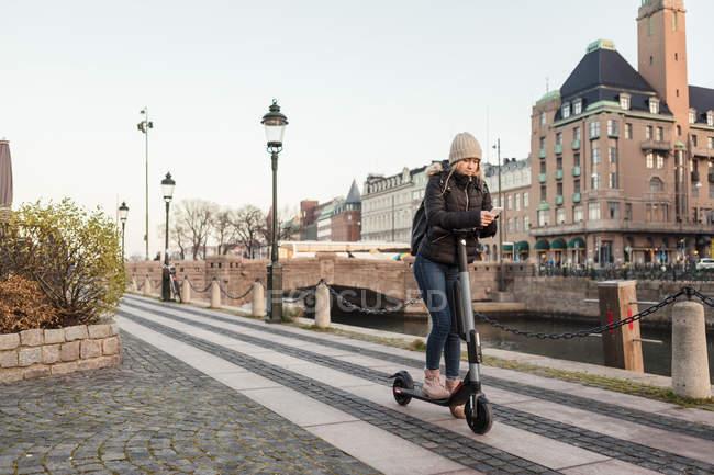 Teenagermädchen schreibt SMS auf Smartphone, während sie mit dem E-Scooter auf der Straße am Kanal in der Stadt gegen den Himmel fährt — Stockfoto