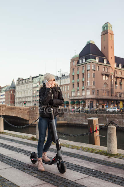 Full length of teenage girl talking on mobile phone while standing on e-scooter by canal in city — Stock Photo
