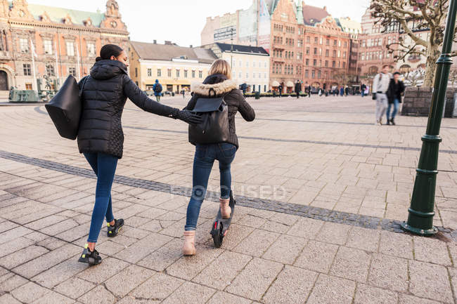 Amigo empujando a adolescentes en scooter electrónico por la calle de la ciudad. - foto de stock