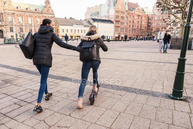 Friend pushing teenage girl riding e-scooter on city street — Photo de stock