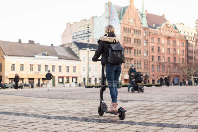 Largometraje de adolescencia montando scooter eléctrico en la calle de la ciudad. - foto de stock