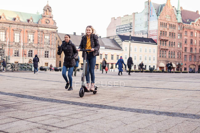 Friend walking behind teenage girl riding e-scooter on street in city — Stock Photo