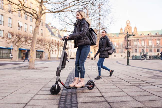 Amigo mirando a la adolescente montando e-scooter en la calle en la ciudad durante el invierno. - foto de stock