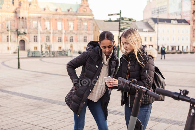 Teenage girl showing mobile phone to friend while standing by e-scooter at city — Stock Photo