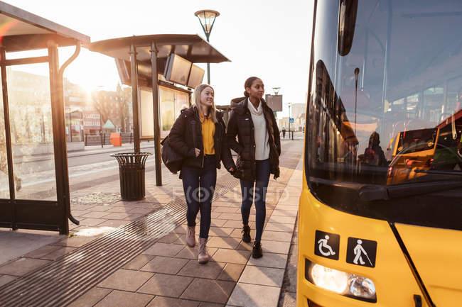 Freunde laufen in der Stadt auf Fußweg in Richtung Bus — Stockfoto