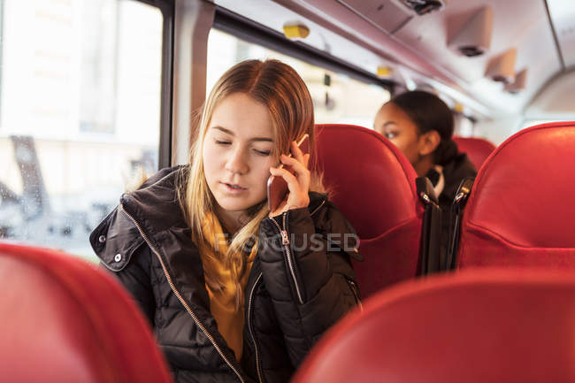 Teenage girl talking on smart phone while sitting in bus — Stock Photo