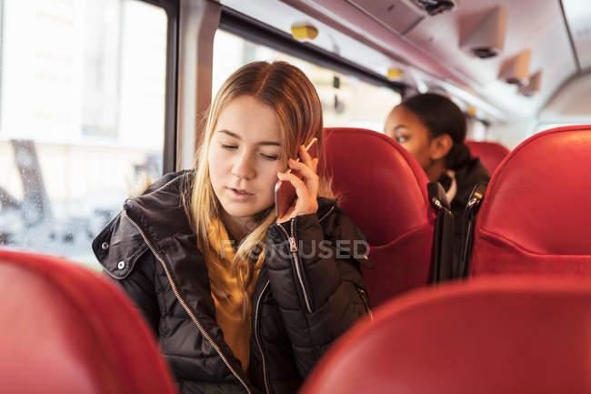 Teenagermädchen telefoniert im Bus — Stockfoto