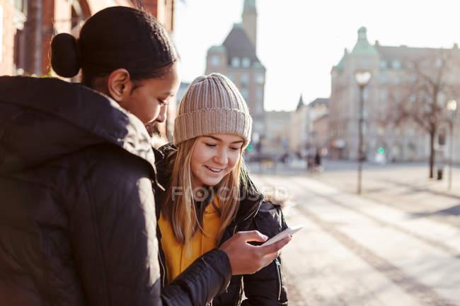 Ragazza adolescente che mostra il telefono cellulare ad un amico in città — Foto stock