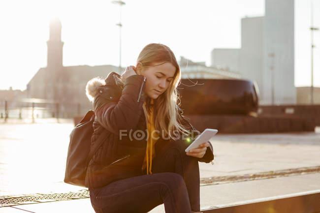 Adolescente utilizando el teléfono inteligente mientras está sentado en los pasos durante el día soleado - foto de stock