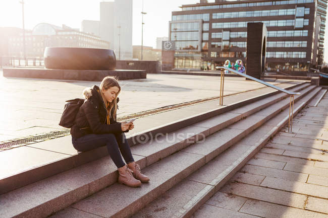 Full length of teenage girl using mobile phone while sitting on steps in city — Stock Photo
