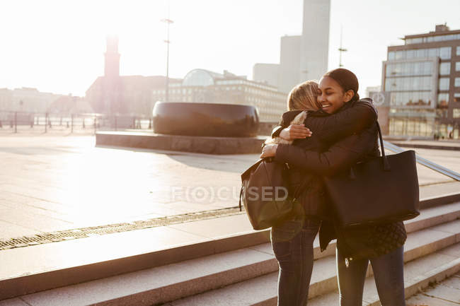 Multi-ethnic teenage friends embracing by steps while greeting in city during winter — Stock Photo