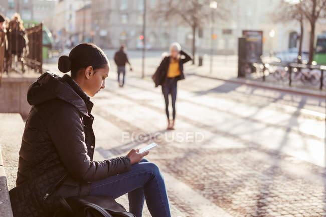 Ragazza adolescente utilizzando il telefono cellulare mentre seduto su gradini in città — Foto stock