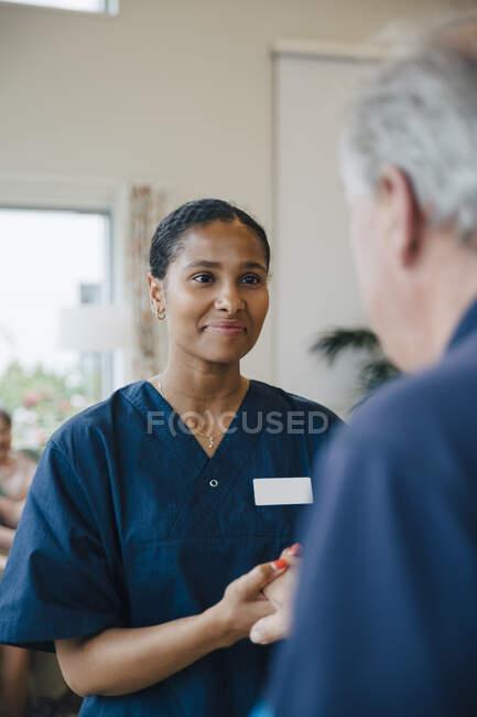 Lächelnde Hausmeisterin hält Rentnerin im Pflegeheim die Hand — Stockfoto